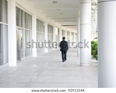 business people walk on the corridor of modern building. rear view
