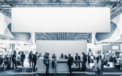 business people walking between trade show booths at a public event exhibition hall, with banner and copy space for individual text