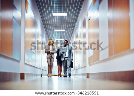 Business people walking down the office corridor and communicating