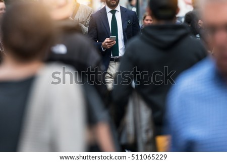 Business people walking from the job in busy city street. Elegant businessman in the people crowd walking and texting on the phone. #511065229