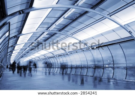 Business People walking in a futuristic tunnel. Shot with slow shutter speed to create blur effect