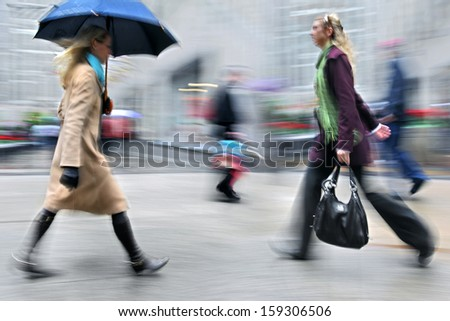 business people walking in the street on a rainy day motion blurred #159306506