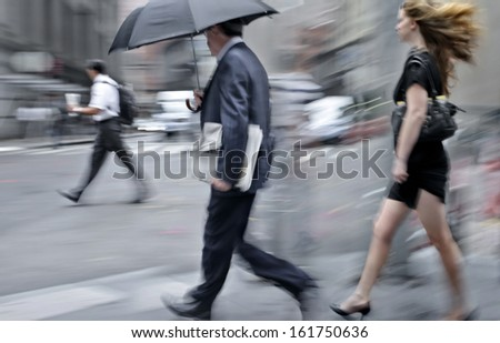 business people walking in the street on a rainy day motion blurred #161750636