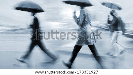 business people walking in the street on a rainy day motion blurred and blue tonality