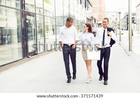 Business people walking trough passage, looking each other and smiling.