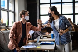 Business people with face masks greeting indoors in office, coronavirus concept.
