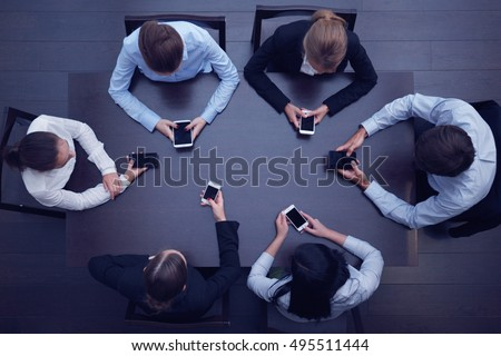 Business people with smartphones sitting around the table, top view - Shutterstock ID 495511444