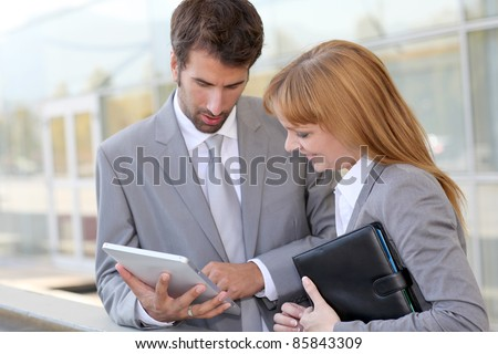 Business people working outside on electronic tablet