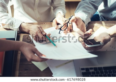 Business people working together. Loft office and smart casual dress code. Researching new product strategy. Electronic devices and paperwork on the table #617698028