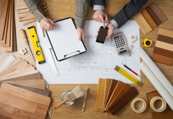 Business people working together on a building project, desktop top view with tools, wood swatches, mobile phone and blueprint