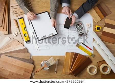 Business people working together on a building project, desktop top view with tools, wood swatches, mobile phone and blueprint ストックフォト ©