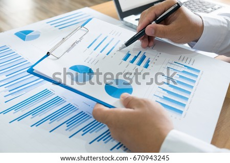Business person analyzing financial statistics displayed on the spreadsheet data  #670943245