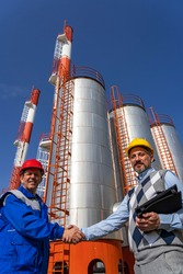 Business Person and Worker in Uniform Shaking Hands Against Power Plant Chimneys and Storage Tanks. Man in Personal Protective Equipment Meeting with Businessperson. Business Relationship Concept.