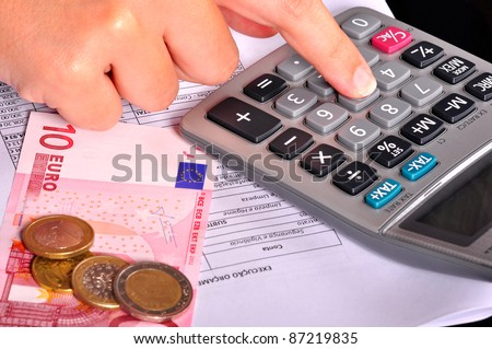 Business person doing accounts using a calculator with some money on the side