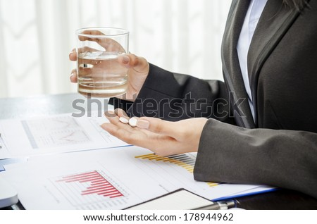 Business person holding medicine and glass of water