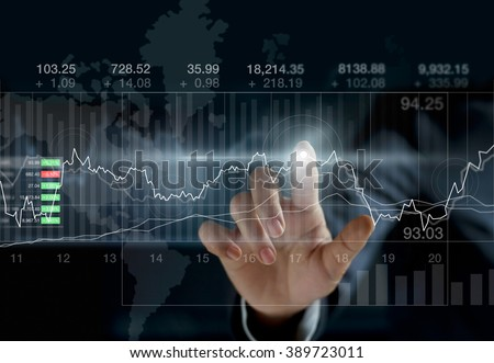 Business person touching charts and diagrams stock market on dark background