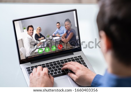 Business Person Videoconferencing With Colleagues On Laptop