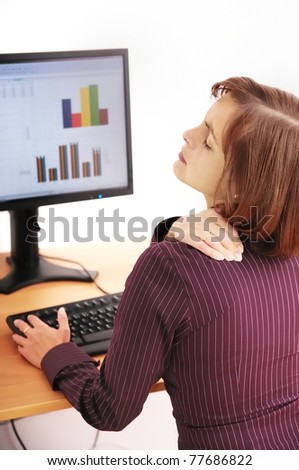Business person with neck pain. Focus on hand on neck with blurred monitor on table in background.