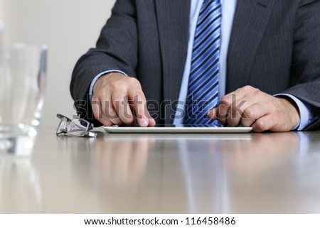 Business person working on digital tablet at office desk - stock photo