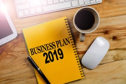 BUSINESS PLAN 2019 CONCEPT. Office desk table with laptop computer and coffee cup . Top view