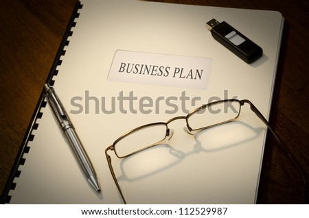 Business Plan on a desk with a pen, a thumb drive and a pair of glasses
