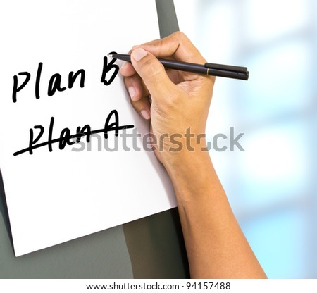 Business plan strategy changing. hand crossing over Plan A, writing Plan B.