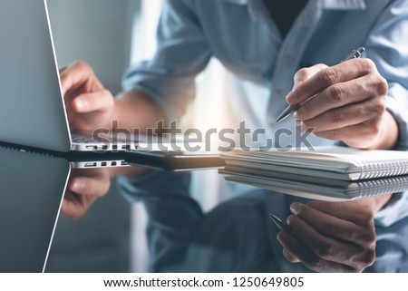 Business planning, E learning concept. Casual business man writing on notebook and working on laptop computer in modern office. Man studying online course via laptop and lecture on notepad.