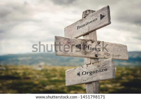 Business, plans and organize wooden signpost outdoors in nature. Quote, message, road, business, success concept. #1451798171