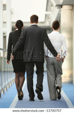 Business portrait of tree persons - young man and two women being touched by a man in modern office corridor