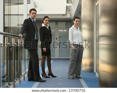 Business portrait of tree presons - young man and two women standing on modern office corridor