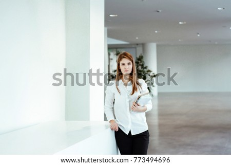 Business portrait. The young woman with a long fair hair in white office shirt costs against the background of business center and holds the tablet and the daily log in hand. #773494696