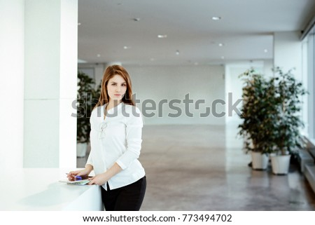 Business portrait. The young woman with a long fair hair in white office shirt costs against the background of business center and holds the tablet and the daily log in hand. #773494702