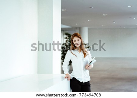 Business portrait. The young woman with a long fair hair in white office shirt costs against the background of business center and holds the tablet and the daily log in hand. #773494708