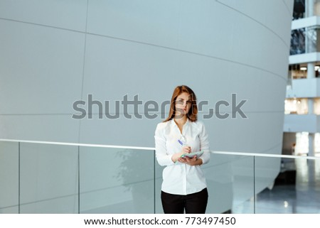 Business portrait. The young woman with a long fair hair in white office shirt costs against the background of business center and holds the daily log in hand. #773497450