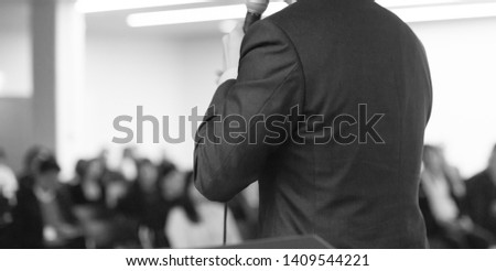 Business presentation being given by tech executive. Black and white photo of corporate seminar with speaker presenting to audience. Lecture speech presenter. Leadership training coach in workshop.  #1409544221