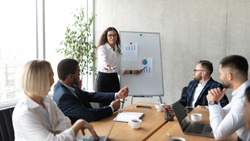 Business Presentation. Mexican Businesswoman Giving Speech Pointing At Blackboard With Graphs And Charts During Corporate Meeting With Colleagues In Modern Office. Panorama, Selective Focus