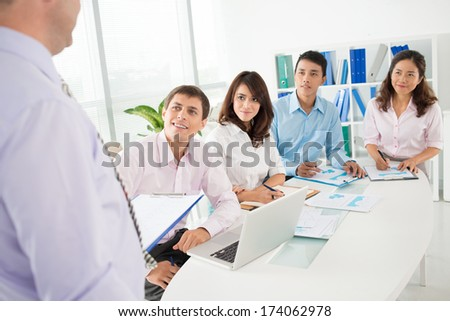 Business presentation where the CEO explaining the working plan to his co-workers on the foreground