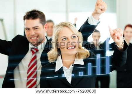Business - presentation within a team; a female colleague shows graph or chart on screen