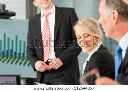 Business - presentation within a team, a male, colleague is standing on the flipchart
