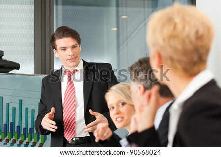 Business - presentation within a team; a male, colleague is standing on the screen