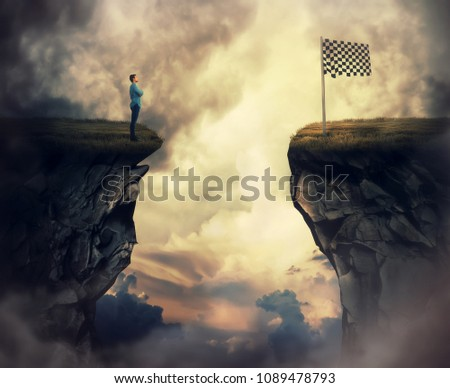 Business problem as a young man stand on a cliff need to go the other side to reach the finish flag. Overcome problems, successful planning and goal achievement.