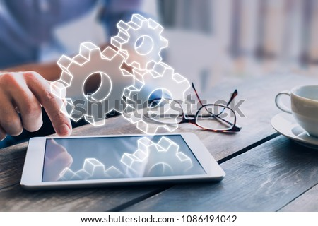 Business process management automation concept using internet technology and ERP (Enterprise Resource Planning) to improve productivity and efficiency, businessman touching computer screen, AR gears