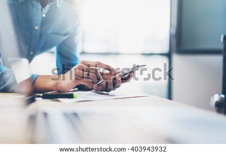 Business process photo. Account manager using mobile phone. Typing contemporary smartphone screen. Horizontal. Film effect. Blurred background #403943932