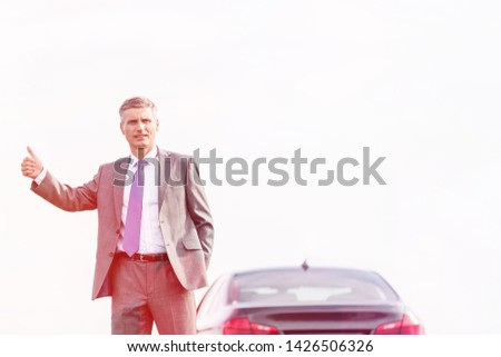 Business professional hitchhiking by breakdown car against sky #1426506326