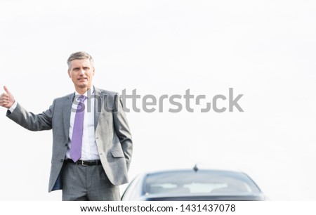 Business professional hitchhiking by breakdown car against sky #1431437078