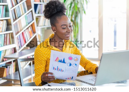 Business professionals. Business woman analyzing data using computer while spending time in the office. Beautiful young grinning professional Black woman in office. Graphs and charts