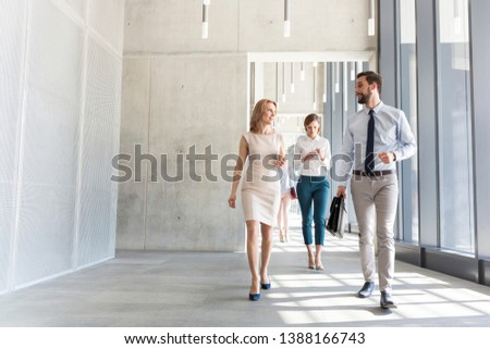 Business professionals talking while walking in office corridor #1388166743