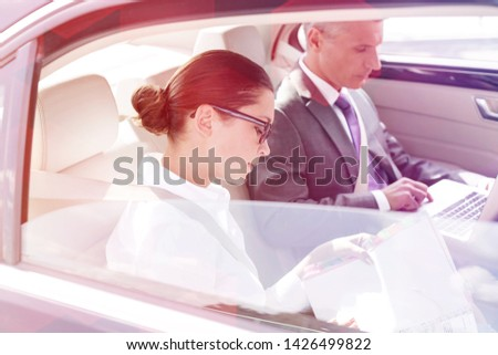 Business professionals working on laptop and documents car #1426499822