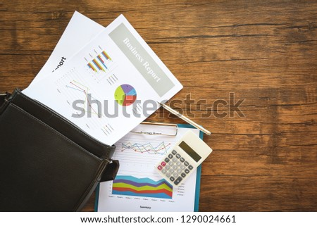Business report chart preparing graphs on briefcase bag / Summary report in Statistics circle Pie chart on paper business document financial and calculator pen on the wooden table background Foto d'archivio ©