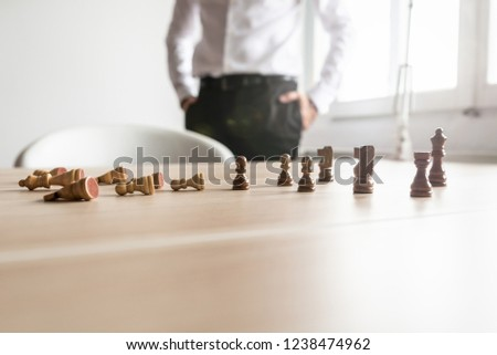 Business rivalry concept - white chess pieces lying fallen and black figures standing on office desk with businessman standing beside. #1238474962